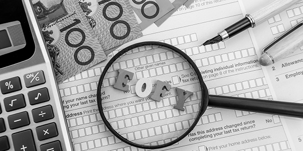 """Stock image of """"EOFY"""" tiles onAustralian tax forms with Magnifying glass, pens, money and calculator"""