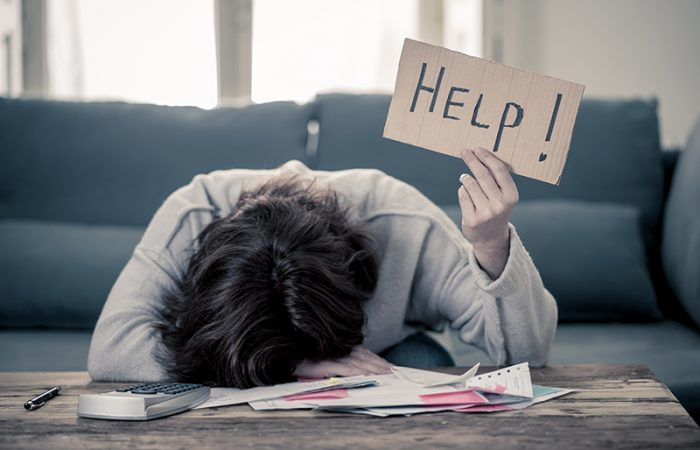 Stock image of upset young woman with head on desk holding up a HELP! sign while doing finances